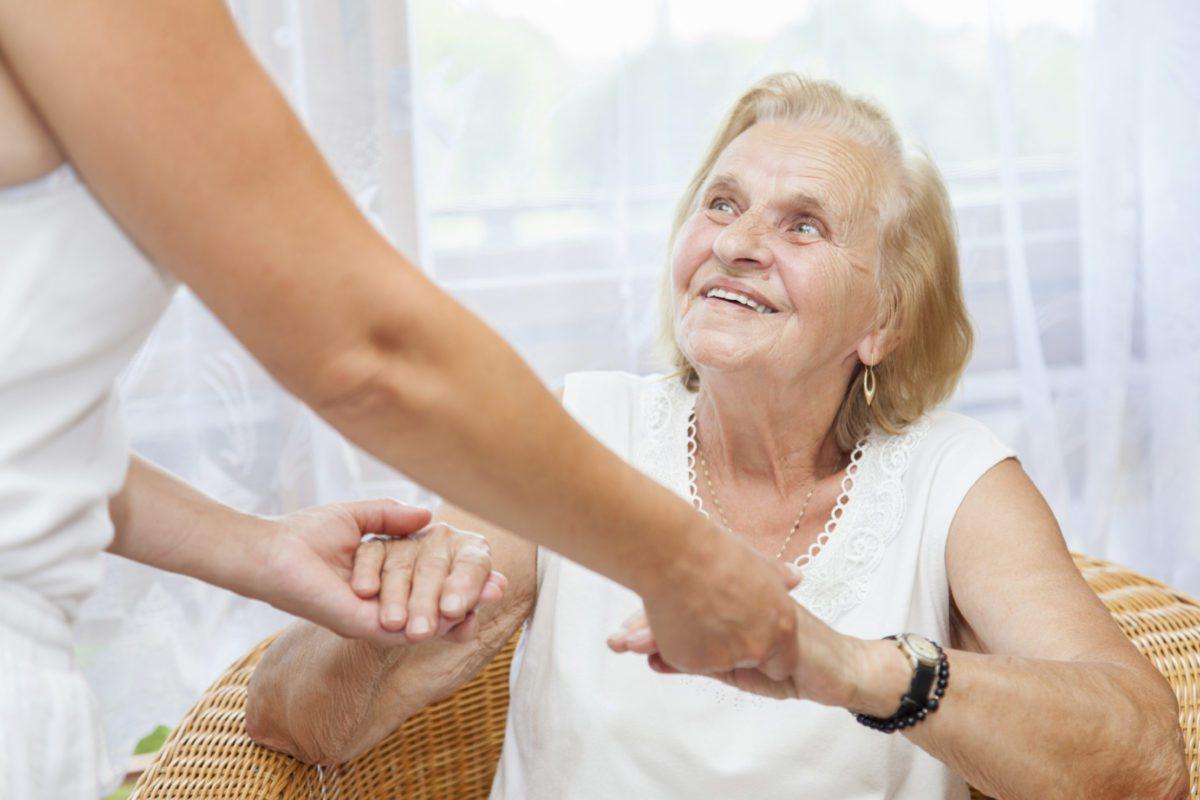 nursing helping an elderly woman stand up