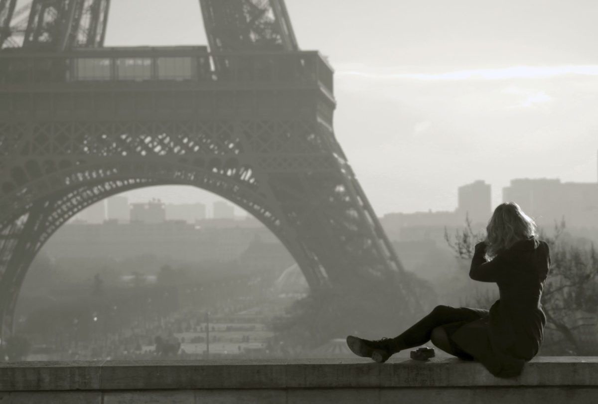 woman sitting at the base of the Eiffel Tower