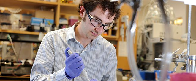 Nate Cira works in a lab with a pipette