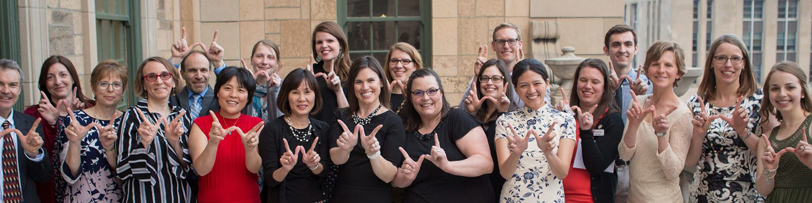 "Staff members from UW-Madison's Adult Career & Special Student Services office post making the ""W"" with their hands"