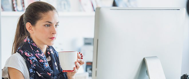 Woman working on computer while drinking coffee