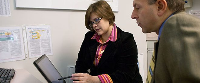 Educator pointing something out to colleague on a tablet screen