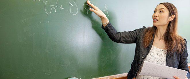 Professor pointing to equation on blackboard