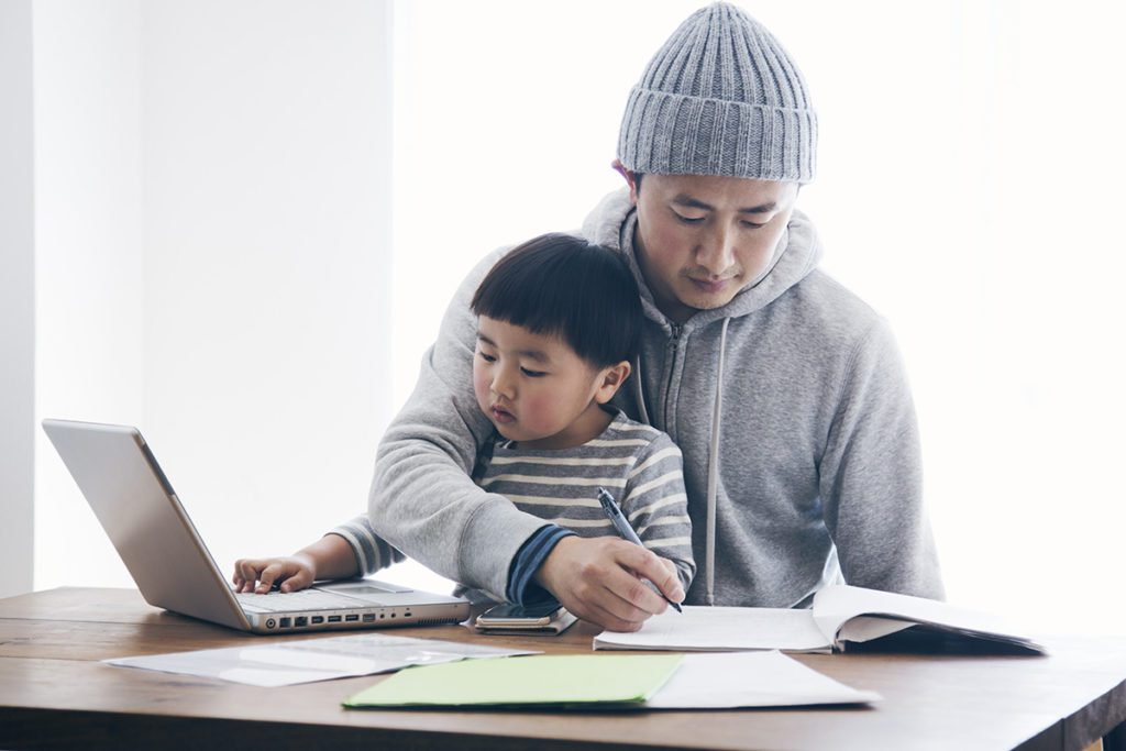 dad studying with his son on his lap