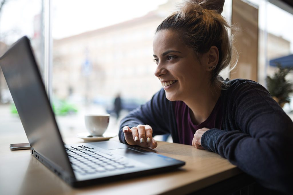Smiling young woman works on laptop