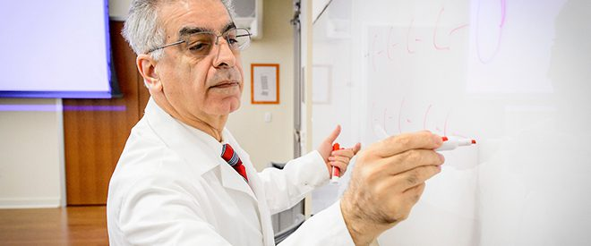 Materials Science professor writing on white board
