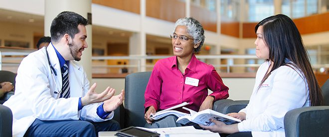 a group of nursing professionals talk in the lobby of the UW-Madison Nursing School