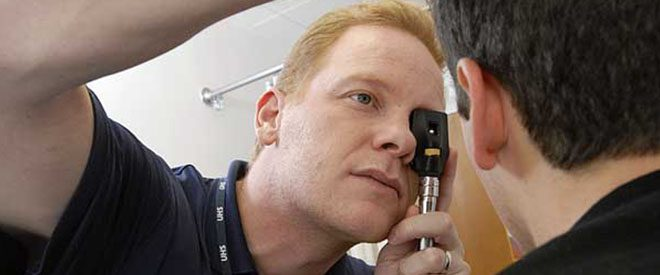 Physicians assistant checking patients eyes