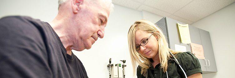 nurse tests a patients reflexes