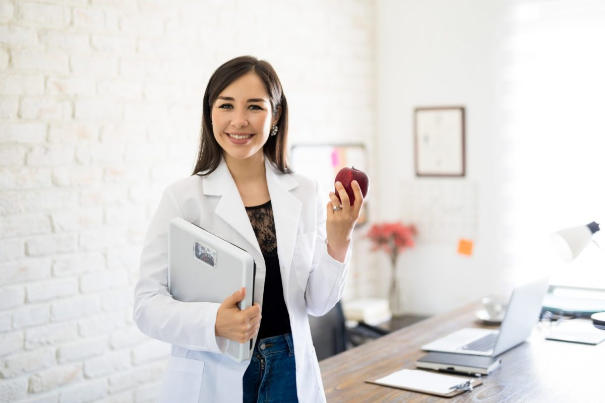 Portrait of young smiling female nutritionist holding weight scale and apple in the consultation room