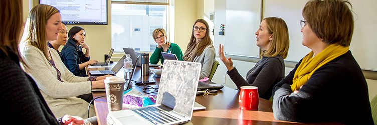 a group of PhD Nursing students have a discussion around a table.