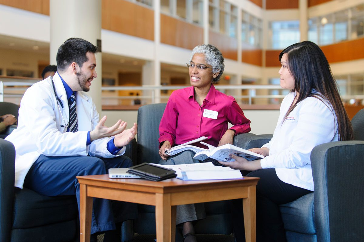Three health care professionals converse around a table.