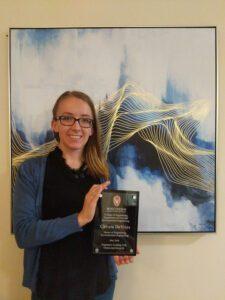 Christa DeVries holds a plaque in front of framed artwork.