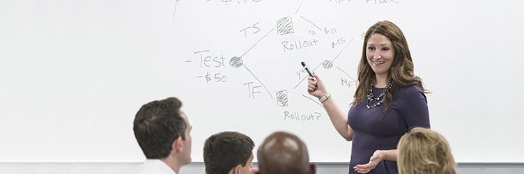 MBA student gives a presentation at the whiteboard