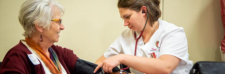 A UW–Madison DNP student takes a woman's blood pressure.