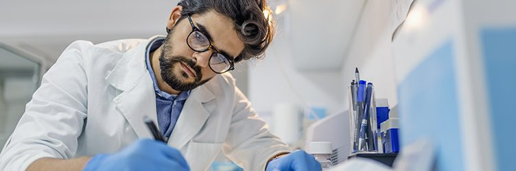 A man in a lab coat writes at a desk.