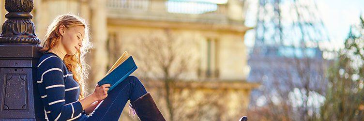 A woman reads a book on a bridge near the Eifel Tower in Paris.