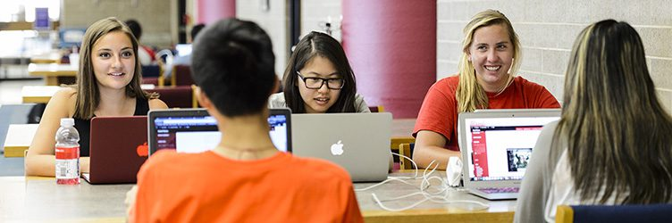 Students work together on laptops in Helen C. White library at UW–Madison.