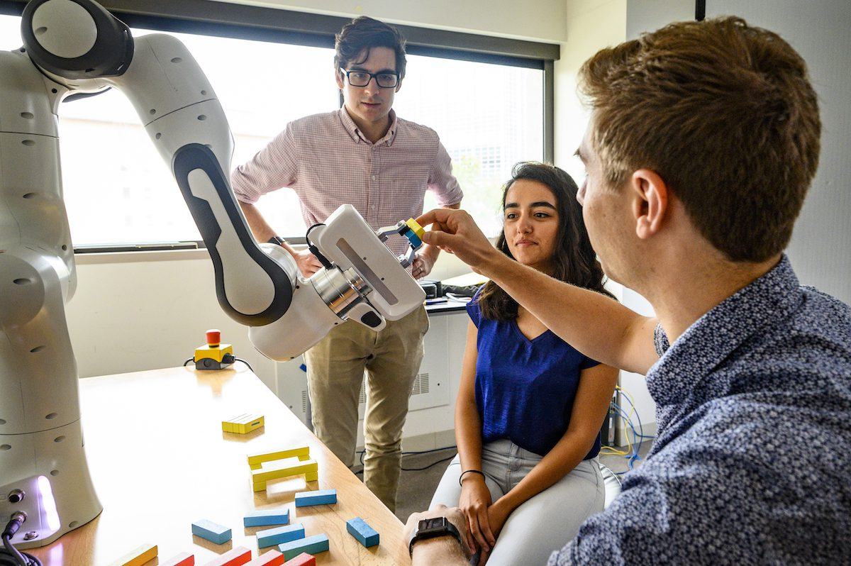 Graduate students working in lab with a robotic arm