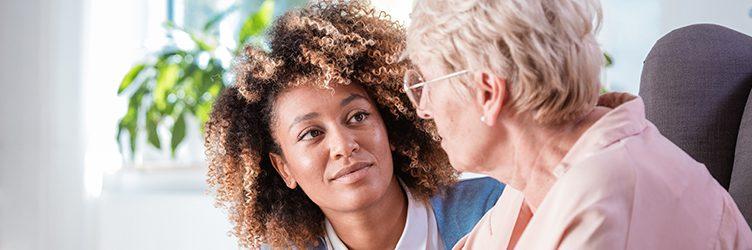 A social worker talks to an elderly client.