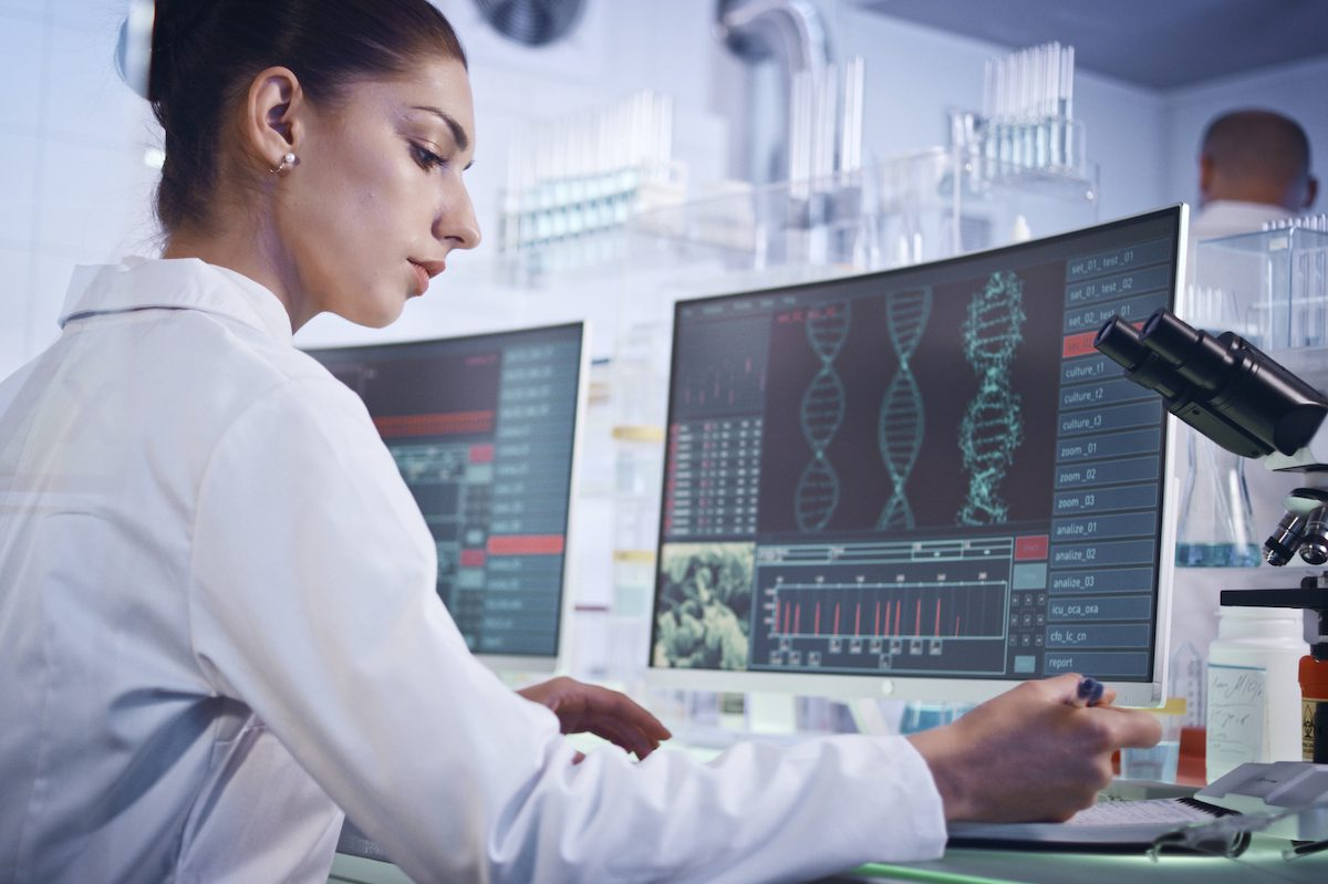 Female scientist studying DNA helix on computer